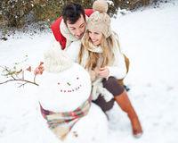Paar im Winter baut einen Schneemann