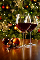 Glasses of red wine on table with Christmas tree