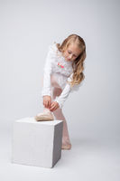 Curly little girl tying pointe, on gray backdrop