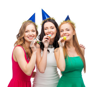 three smiling women in hats blowing favor horns