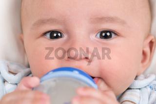 Baby trinkt Milch und hält die Flasche