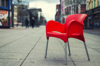a red chair sits on an empty road