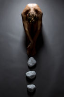 Top view of sensual nude woman and stones