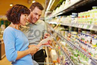 Verkäufer hilft Frau mit Einkaufsliste im Supermarkt