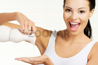 Attractive woman spilling oil on hand.