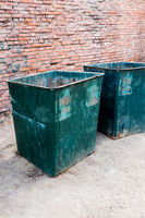 Angle vertical view of a two green dustbins outside against red brick wall