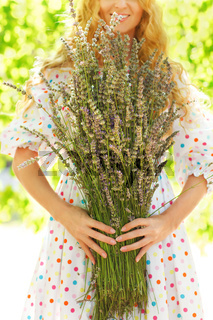 Romantic woman with long blond hair with lavender bouquet