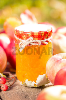 Apple jam and fruits on wooden table