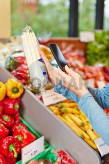 Kunde im Supermarkt scannt Barcode von Spargel