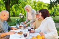 Familie mit Senioren isst Kuchen im Garten