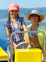Mother with her daughter in a motorboat.