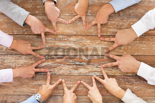 close up of business team showing victory gesture