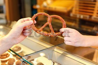 Shopkeeper in bakery sells pretzel