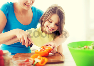 smiling little girl with mother chopping pepper