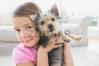 Smiling little girl holding her yorkshire terrier puppy