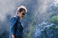Nepalese woman standing next to a waterfall