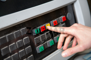 Worker pressing a stop button on a control panel
