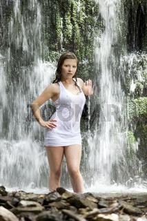 Junge Frau steht im Wasserfall
