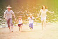 Familie mit Kindern im Sommer am Strand