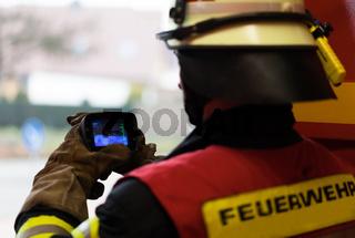 Feuerwehrmann misst Temperatur mit Wärmebildgerät