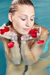 Frau mit Rosenblättern im Pool