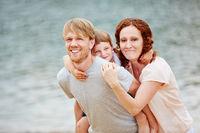 Familie mit Tochter am Meer im Sommer