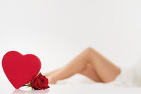 red heart and a rose in front of legs