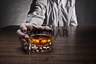Mann greift nach einem Glas Whisky