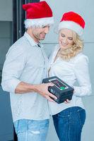 Couple Wearing Santa Hats Exchanging Gift