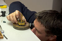 Watchmaker checks parts of a wristwatch