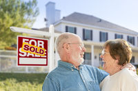 Senior Couple in Front of Sold Real Estate Sign, House