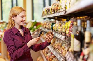 Junge Frau scannt Packung Nüsse im Supermarkt