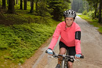 Woman mountain biking through forest road