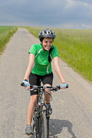 Woman riding bike on cycling path meadow