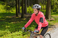 Woman mountain biking in forest sunny day