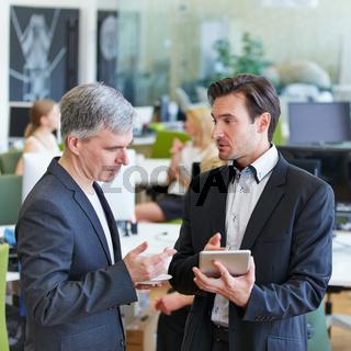 Geschäftsleute reden über Tablet Computer im Büro