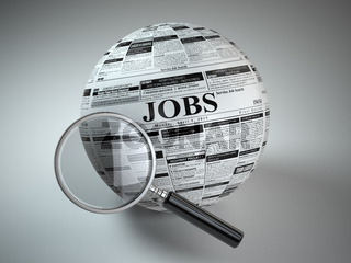Concept of job search . Newspaper sphere and loupe.