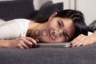 Smiling young woman resting on a laptop