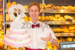 Baker with wedding cake in confectionery