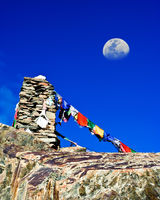 Buddhist stone tower with praying flags and moon at Himalaya high mountain road pass at Manali - Leh highway over blue sky. India, Ladakh, altitude 4500m