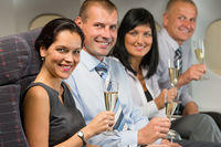 Business people flying airplane drink champagne