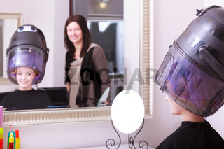 Girl relaxing with hairdryer by hairstylist in hair beauty salon. Mirror.