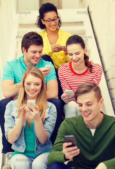 smiling students with smartphone texting at school