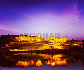 Vintage retro hipster style travel image of Amer Fort (Amber Fort) illuminated at night - one of principal attractions in Jaipur