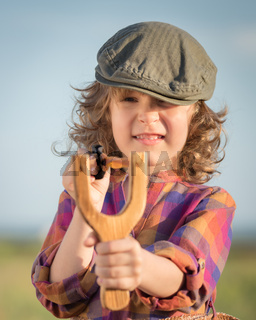 Funny kid shooting wooden slingshot