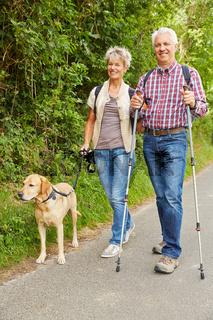 Mann und Frau gehen Gassi mit Hund