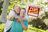 Couple In Front of Sold Real Estate Sign Holding Keys