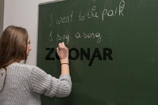 Teenager schreibt Englisch an die Tafel