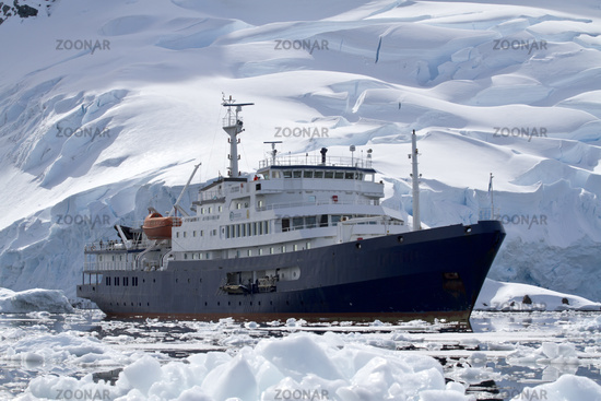 big blue tourist ship in Antarctic waters against the backdrop of glaciers