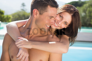 Romantic woman embracing man by swimming pool
